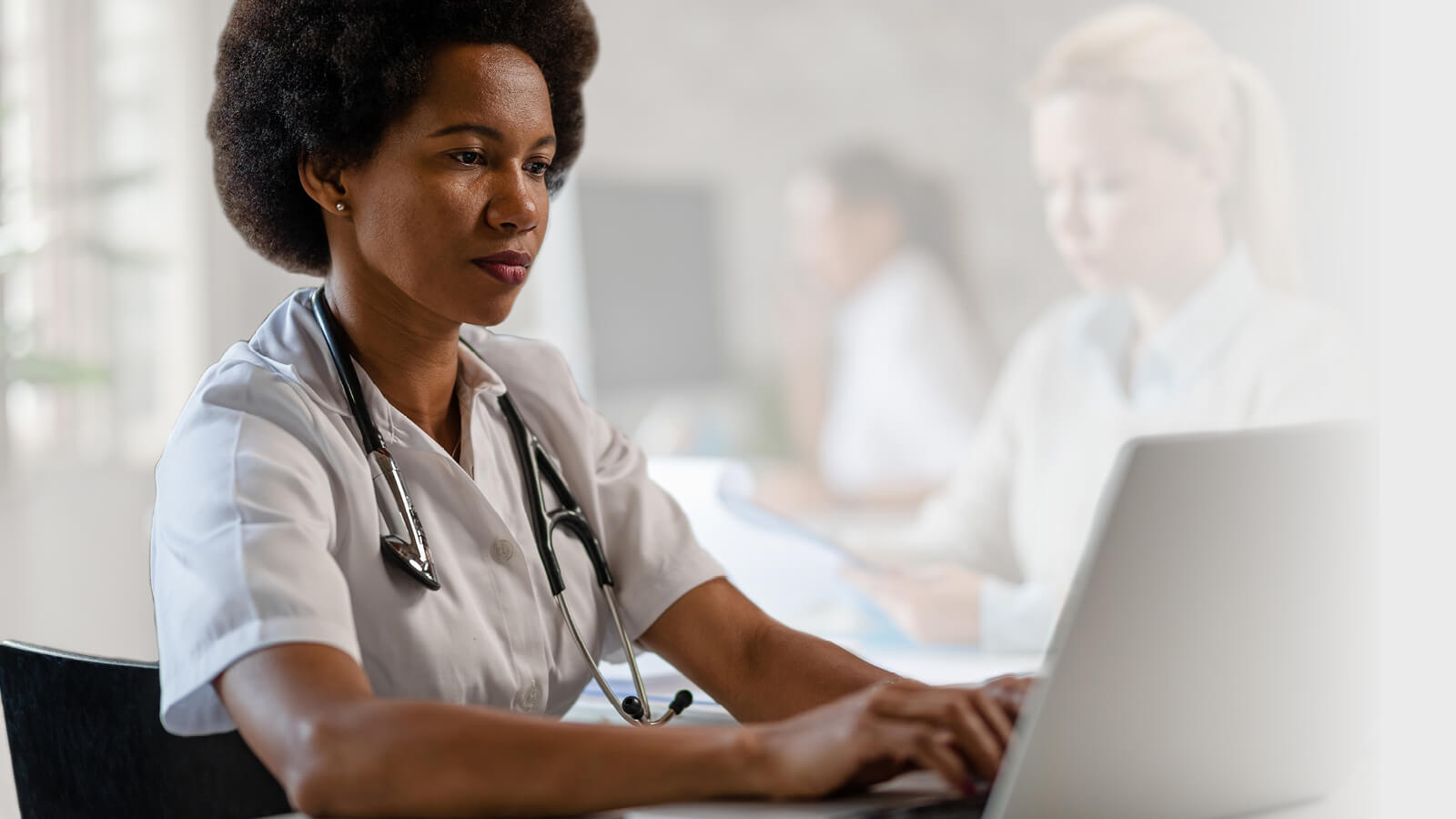 An image of a NHS healthcare professional typing on a laptop showing that Microsoft Teams gets you together.